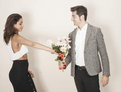 Woman accepting a bouquet from her date Stock Photos
