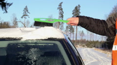 Man on the road cleans with brush the car out of the snow Stock Footage