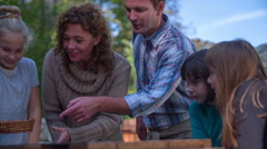 Couple playing with the children the treasure hunt Stock Footage