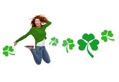 Smiling teenage girl jumping in air with shamrock Stock Photos