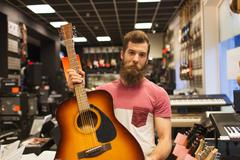 Assistant or customer with guitar at music store Stock Photos
