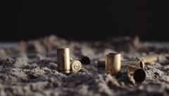 Slow motion 9mm bullet shells falling in to sand Stock Footage