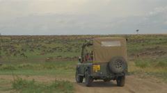 Tourists on a game drive observing the great migration Stock Footage
