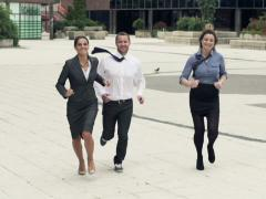Happy businesspeople in hurry, running through pavement in city, slow motionNTSC Stock Footage