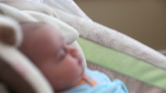 A newborn baby boy in a swing at home Stock Footage