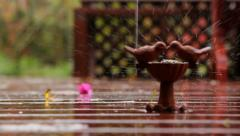 Rain falls on stone bird bath on beautiful wooden deck Stock Footage