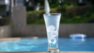 Stock Video Footage of Water Flowing into Glass with Ice near Swimming Pool. Slow Motion.