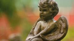 Rain falls around an angel cherubim stone statue in a garden Stock Footage