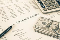 Stock Photo of money and income statement report in sepia tone
