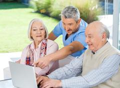 Male Caretaker Assisting Senior Couple In Using Laptop Stock Photos