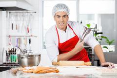 Confident Chef Holding Tongs While Preparing Ravioli Pasta In Ki - stock photo