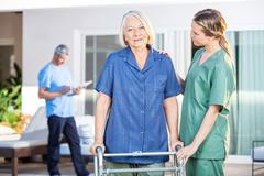 Nurse Assisting Senior Woman To Walk With Zimmer Frame - stock photo