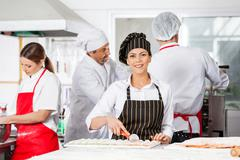 Smiling Chef Cutting Ravioli Pasta With Colleagues In Background - stock photo