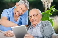 Nurse And Senior Man Enjoying While Using Tablet Computer - stock photo