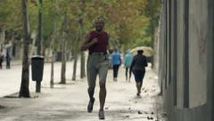 Funny, happy man jogging in city during rain, slow motion shot at 240fps HD Arkistovideo