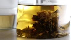 Pouring green tea  into glass teapot Stock Footage