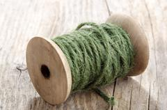 Vintage wooden spool with green sisal Stock Photos