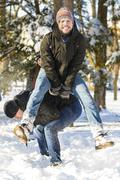 People playing jumping over another person in wintertime - stock photo