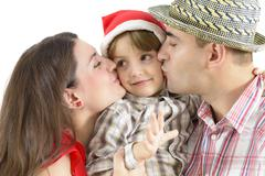 Mom and dad kissing their little boy Stock Photos