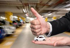 Man in black suit holding small car model and showing ok sign Stock Photos