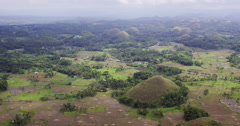 Aerial of the famous Bohol Chocolate Hills with harvested rice fields Stock Footage