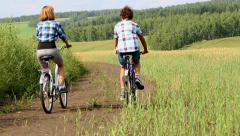 Walk on Bicycles,  Man and woman ride bicycles on a country road - stock footage