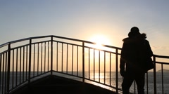 Man's silhouette walking along the fence against ocean at sunset Stock Footage