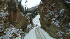 4K Aerial Footage Flying Between Rocks Above Mountain Road in Winter Stock Footage