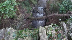 4K very small stream filmed from stone bridge, a log going over the stream Stock Footage