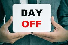 businessman with a signboard with the text day off - stock photo