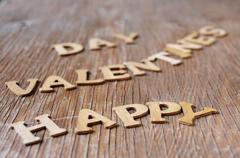 letters forming the sentence happy valentines day on a wooden surface - stock photo