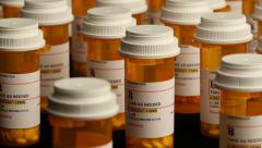 Pan down on field of prescription pill bottles. 4K - stock footage