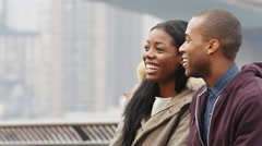A couple sits on a bench in a park in front of the brooklyn bridge on an - stock footage