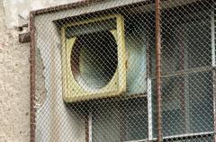 Ventilator behind the iron bar, old building. Stock Photos