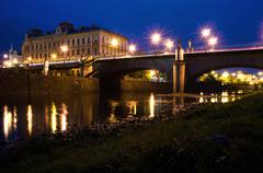 panorama of bridge, river and school with lights at night. - stock photo