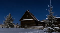 Timelapse HD of stars over timber house at winter night, camera moving down Stock Footage