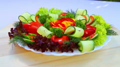 Cutting a variety of fresh, juicy vegetables on a white plate. Vegetarian food. Stock Footage