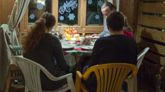 4K. Family celebrating New Year sitting at the table in rural house. Time lapse - stock footage