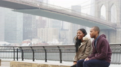Stock Video Footage of A couple sits on a bench in a park in front of the Brooklyn bridge on an