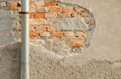 Metal evaes and brick wall with old chapped fasade. Stock Photos