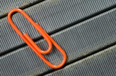 orange paper clip on staple wire background as symbol of solitude. - stock photo