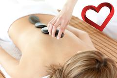 Stock Photo of Composite image of radiant woman having a stone therapy
