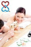 Composite image of young couple lying on a massage table and drinking champagne - stock photo