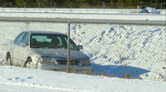 Two Snow Covered Cars in Ditch by Highway - stock footage