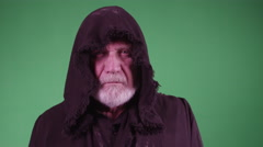 4K Old man in black hooded robe stares forward Stock Footage