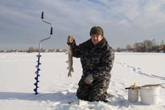 man fishing pike on live bait in winter - stock photo