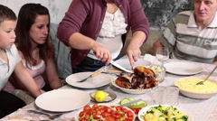 Mother cutting tyrkey for son at dinner table. Thanksgiving dinner - stock footage