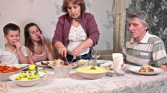 Mother cutting turkey for family which sitting at served table at Thanksgiving Stock Footage