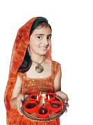 little girl holding a plate of diyas on diwali. - stock photo