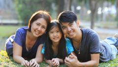 Happy Asian family playing together in park Stock Footage
